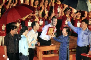 Đại biểu quốc hội Nguyễn Thị Doan  đội ô lên tặng ảnh Bác Hồ cho Nick ở sân VĐ Mỹ Đình khi trời đang mưa.(23/5/2013)